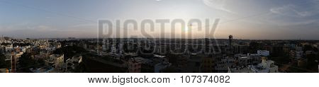 Panoramic aerial or rooftop view of thickly populated Asian city captured just before dusk
