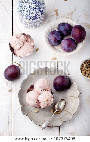 Plum ice cream with cardamon seeds. White background.
