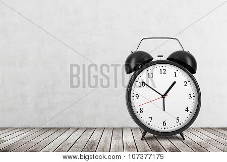 A Black Alarm Clock Is On The Wooden Floor. Concrete Wall.