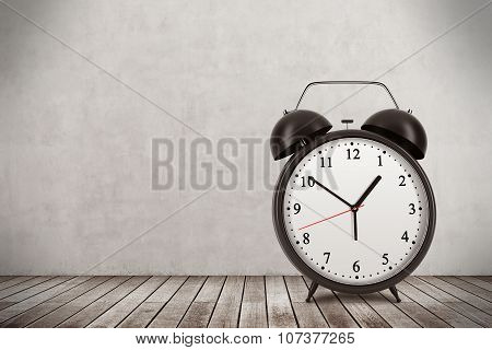 A Black Alarm Clock Is On The Wooden Floor. Concrete Wall. Toned Image.