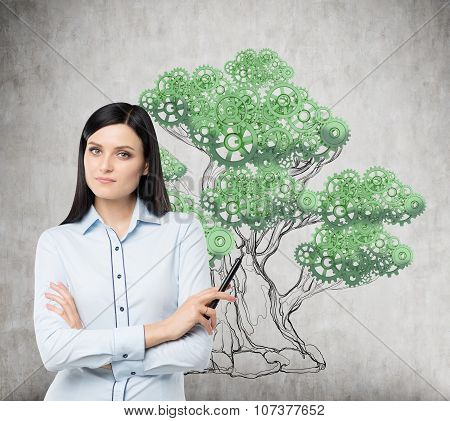 A Brunette Woman In Formal Clothes Holds A Felt-tip Pen Or A Pointer. A Tree Is Sketched On The Conc