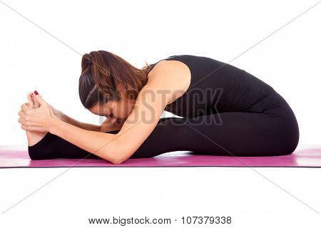 Beautiful woman doing Paschimottasana  pose on yoga class. Studio shot.