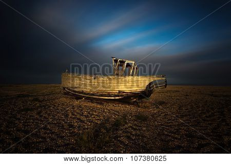 Wrecked ship in sunset at Dungeness beach, England, UK