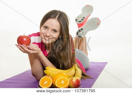 Sportswoman Lying On A Mat, Holding An Apple In Hand, It Is Faced With A Plate Of Fruit