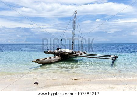 Traditional wooden outrigger canoe floating on the water on tropical white sand beach o South Pacifi