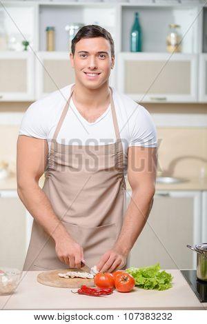 Tough guy chops vegetables in kitchen.