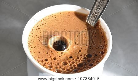 Coffee mug with froth and big bubble