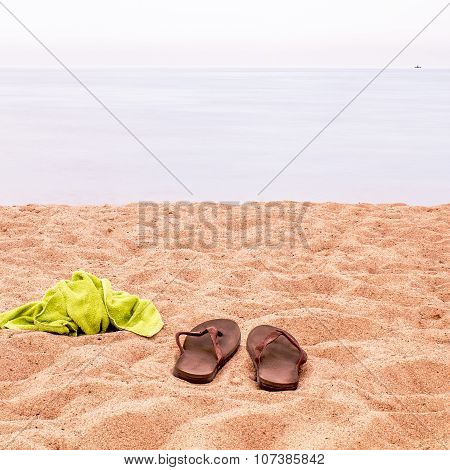 And Slippers And A Towel Left On The Sand On The Beach