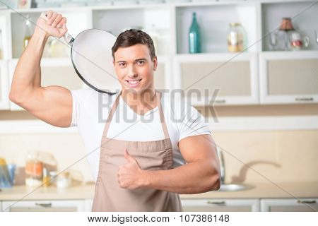 Young attractive cook showing thumbs up.