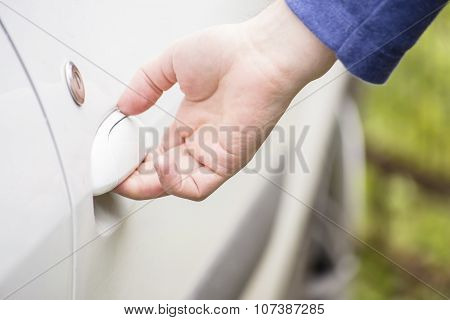 Man Opens The Door Of A White Car Outdoors
