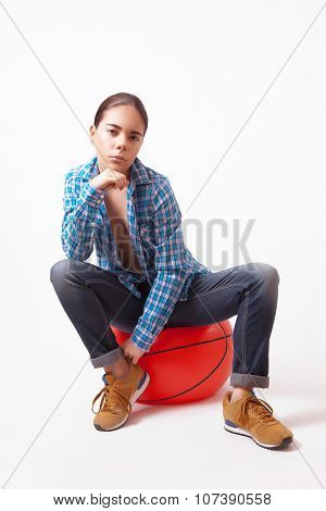 Girl Woman In A Blue Shirt And Jeans Sitting On The Ball