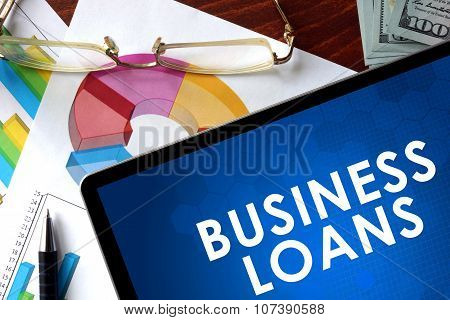 Tablet with business loans on a table.