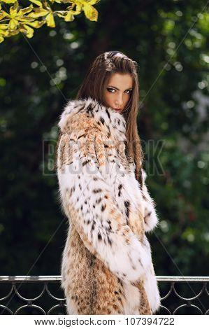 Beautiful European Girl In Luxury Lynx Fur Coat Posing Outdoors