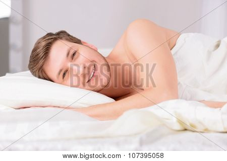Young man in bed lying on the side.