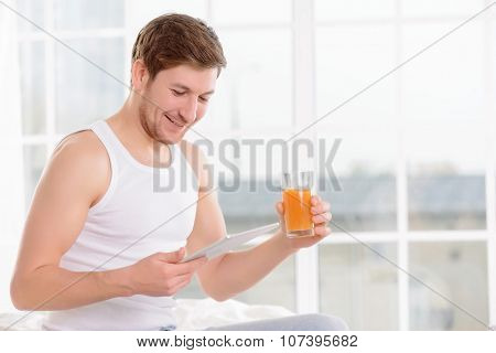 Man checks his planner while drinking juice.
