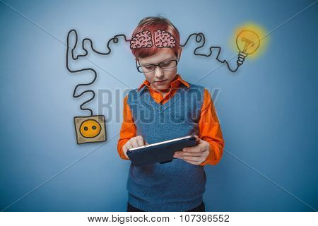 Teen boy with glasses working on a tablet with enthusiasm chargi