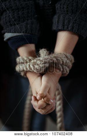 Poor girls standing with tied hands