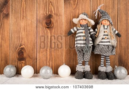 Christmas decorative elves with ball on the snowed wooden background..