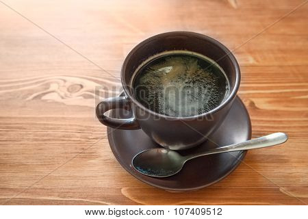 cup of americano on brown wood table