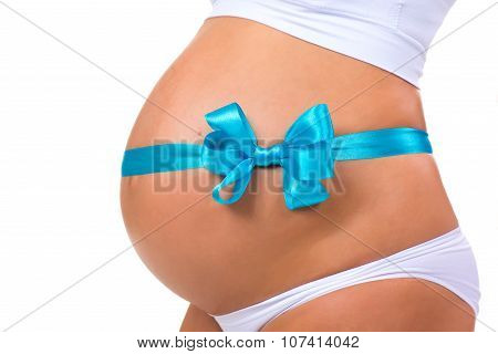Close-up Of Pregnant Belly With  Blue Ribbon And Bow. Concept Of Pregnancy. Newborn Baby Boy.