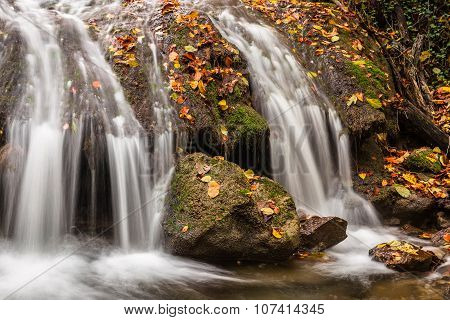 Beautiful Waterfall With Fallen Leaves In The Autumn