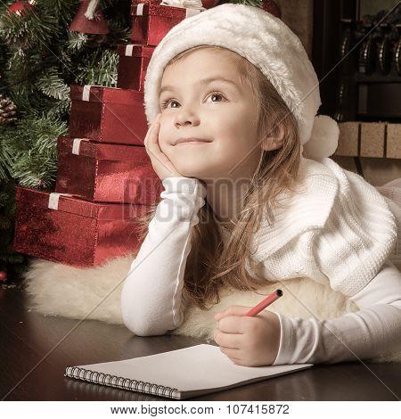 Pretty Girl In Santa Hat Writes Letter To Santa Near Christmas Tree
