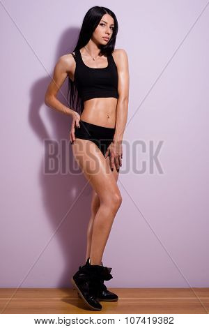 Young woman standing in black sportswear and snickers