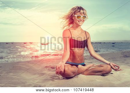Young woman sitting in lotus pose doing yoga on beach with the ocean in the background.