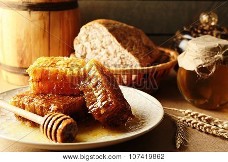 Honeycombs and wooden dipper on plate, fresh bread in basket on wooden background