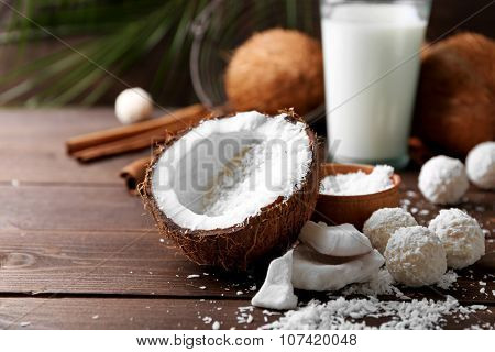 Candies in coconut flakes, glass of milk and fresh coconut on dark wooden background