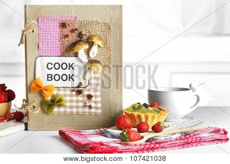 Decorated cookbook with cup of tea and tasty cake on white background