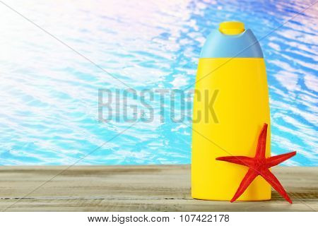 Bottle of suntan cream with sea star on table on water background