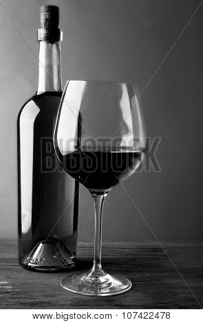 Bottle of white wine and a glass on wooden table,  black and white retro stylization