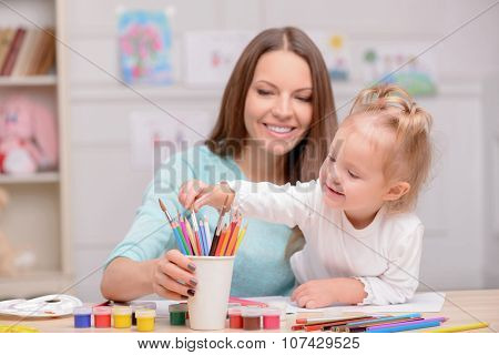 Pretty woman is teaching her child to draw