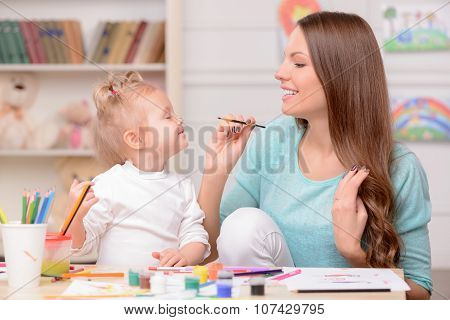 Cheerful friendly family is drawing with joy