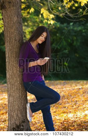 Teen Girl Standing Against Autumn Tree Looking At Cell Phone