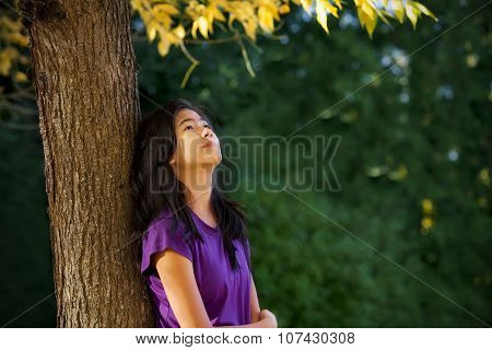 Teen Girl Leaning Against Tree With Autumn Leaves Looking Up