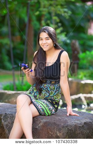 Biracial Teen Girl Sitting On Rock Looking At Cellphone