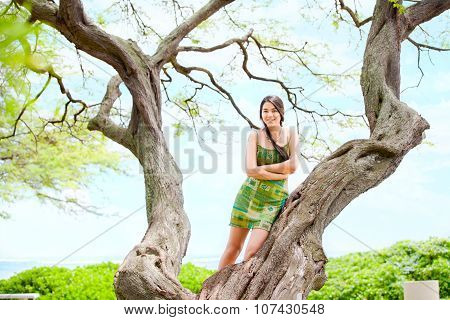 Teen Girl Standing On Large Tree Branch In Hawaii