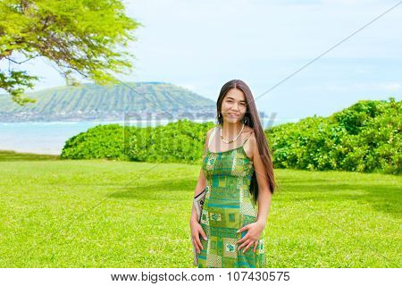 Teen Girl Standing On Lush Green Lawn By Ocean In Hawaii