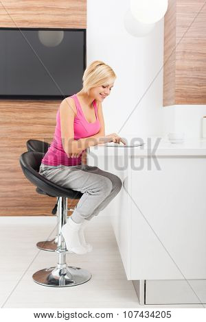 woman tablet sitting table home