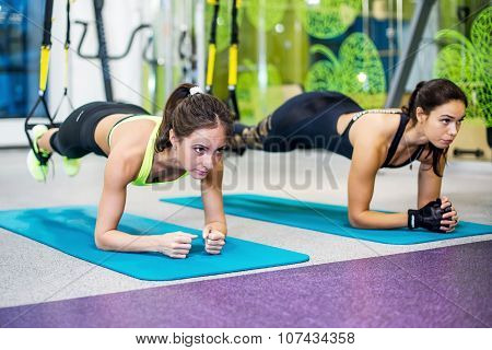 Fit girls in gym doing plank exercise for back spine and posture Concept pilates fitness sport.