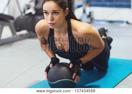 Fit woman exercising with medicine ball workout out arms Exercise training triceps and biceps doing