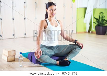 Fit woman doing stretching pilates exercises in fitness studio.