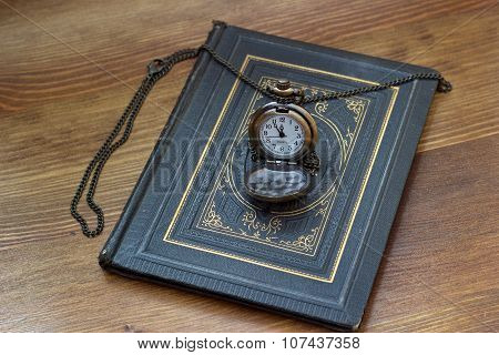 vintage pocket watch lying on the old book
