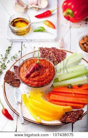 Roasted pepper dip, sauce, spread with fresh carrot, celery sticks