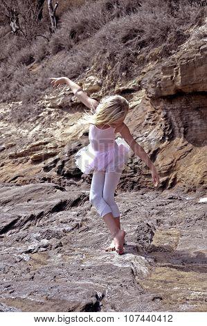 Blonde kid girl in pink leotard barefoot practice ballet dance on the rocks.