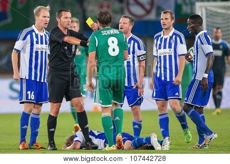 VIENNA, AUSTRIA - AUGUST 28, 2014: Referee Stephane Laurent Lannoy (France) shows the yellow card to Stefan Schwab (#8 Rapid) in an UEFA Europa League qualifying game.