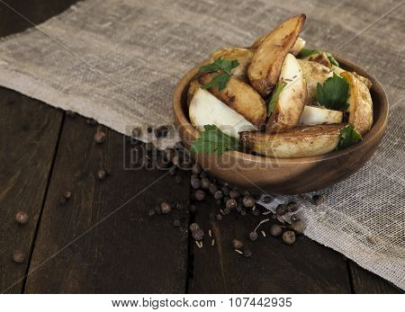 potato wedges in a wooden plate on dark wooden table