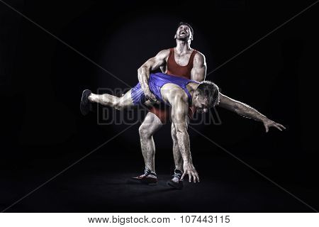 Freestyle wrestler throwing action isolated on black background